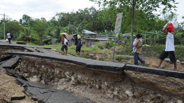 Residents cross a damaged section of a national highway in the central Philippines on February 7.