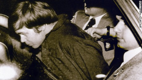 WASHINGTON, UNITED STATES: (FILES): This 30 March 1981 file photo shows John Hinckley Jr. (L) escorted by police in Washington, DC, following his arrest after shooting and seriously wounding then US president Ronald Reagan. A federal judge ruled 17 December 2003 Hinckley can make local visits with his family from St. Elizabeth's Hospital in Washington, DC, where he has been held. AFP PHOTO/FILES (Photo credit should read -/AFP/Getty Images)