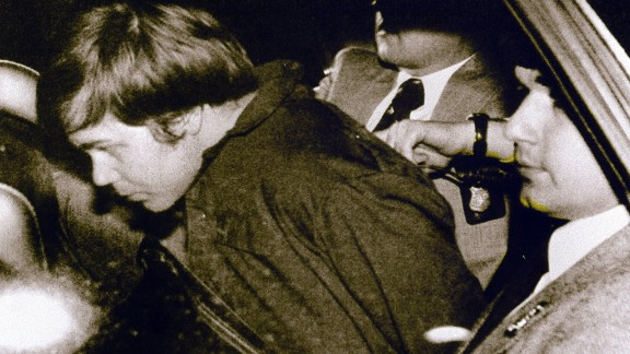 WASHINGTON, UNITED STATES: (FILES): This 30 March 1981 file photo shows John Hinckley Jr. (L) escorted by police in Washington, DC, following his arrest after shooting and seriously wounding then US president Ronald Reagan. A federal judge ruled 17 December 2003 Hinckley can make local visits with his family from St. Elizabeth