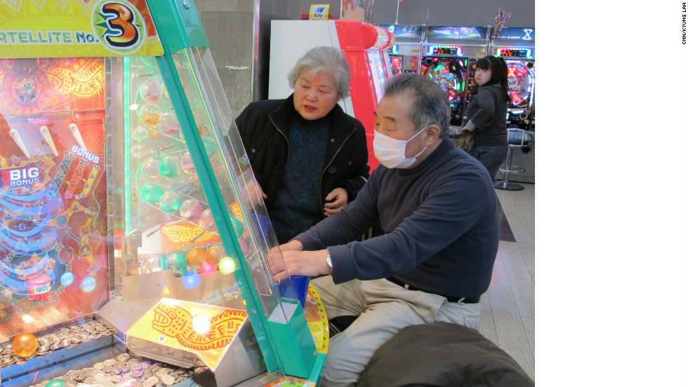 Tsuneko Kataoka, left, watches as another older gamer plays a game.