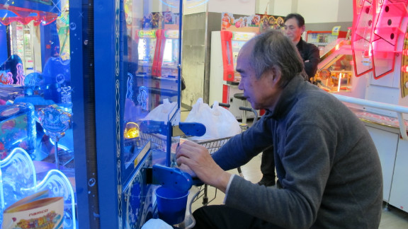 An older gamer plays at the arcade in Yokohama, Japan