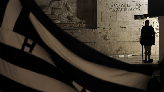 A Greek Presidential guard stands guard behind a Greek flag at the tomb of the Unknown soldier in front of the parliament during a demonstration in Athens