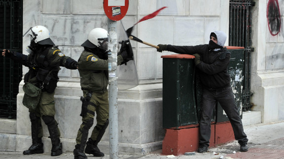 Riot police clash with a demonstrator during the general strike in Athens on February 10, 2012.
