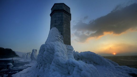 Lighthouse and lampposts are covered with heavy ice in central Adriatic Croatian port of Senj, some 200 kilometres from Zagreb, as the sun sets on February 8, 2012. There are more than 100 villages still trapped by snow in remote, mountain parts in Croatia.