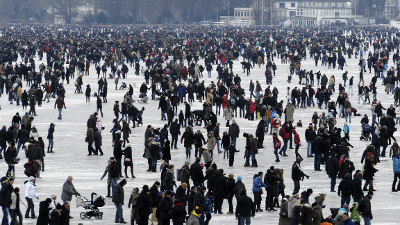 People walk on the frozen Aussenalster river during the