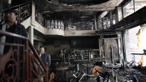 People stand in a damaged building after it burned in central Athens on February 13.  Greek lawmakers approved radical budget cuts to secure a 130 billion euro rescue package aimed at averting bankruptcy, after a day of street battles left dozens injured and Athens buildings ablaze.