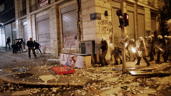 Demonstrators throw projectiles to riot police during violent protests in central Athens