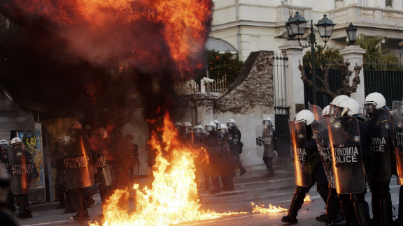 "Demonstrators throw fire bombs to riot police during violent protests in central Athens. Thousands took the streets as the Greek parliament prepared to vote on a new and deeply unpopular EU/IMF austerity deal, to secure a 130 billion euro bailout, aimed at saving Greece from bankruptcy and what Prime Minister Lucas Papademos warned would be ""uncontrollable economic chaos""."