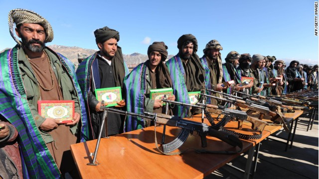 In a file picture taken on January 30, 2012, Taliban fighters stand with their weapons as they hold the Muslim holy book Koran after they joined Afghan government forces during a ceremony in Herat province. The medieval Taliban who ran Afghanistan with the Koran in one hand and a gun in the other now tweet and talk peace, but they remain a potent threat as a NATO withdrawal looms.