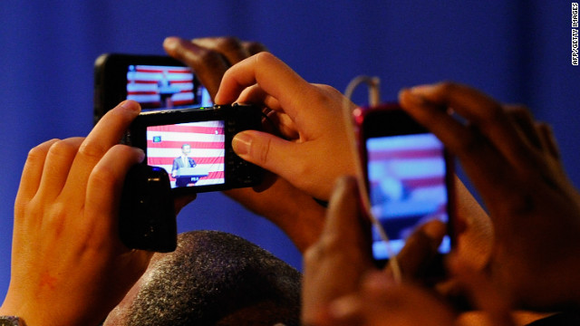 Supporters of President Barack Obama take pictures with their smartphones during a fundraiser in September.