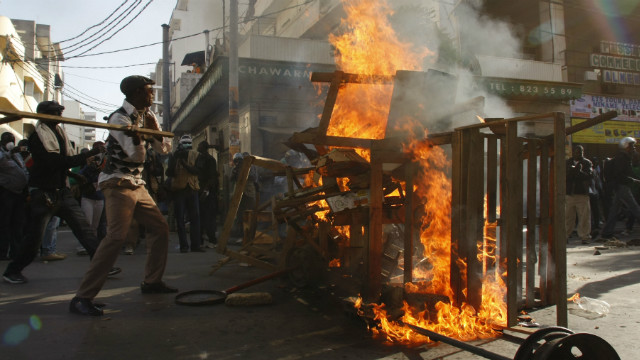 Protesters stand near a burning barricade as they clash with riot police in Dakar on February 18, 2012.