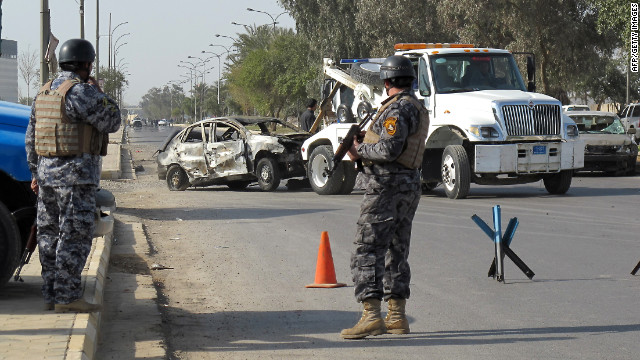 Iraqi policemen stand guard outside a Baghdad police academy that was the target of a suicide car bombing on Sunday.