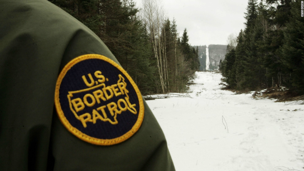 A U.S. Border Patrol agent stands along the boundary marker cut into the forest marking the line between Canadian territory on the right and the U.S.