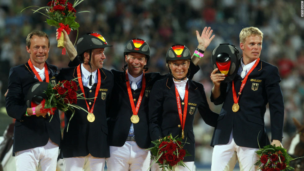 Klimke (second from right) and the victorious German team receive their gold medals at the Beijing Olympics.  Her teammates (left to right) were Peter Thomsen, Andreas Dibowski, Hinrich Romeike and Frank Ostholt.