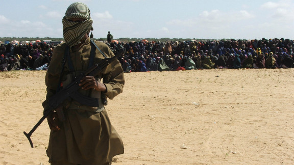 An Islamist fighter stands guard as hundreds of residents watch an amputation punishment carried out. Al-Shabaab