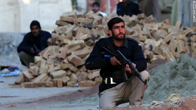 Pakistani policemen take position during a militant attack on a police station in Peshawar on February 24, 2012.