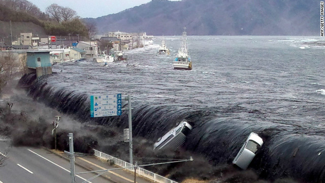This picture taken by a Miyako City official on March 11, 2011 and released on March 18, 2011 shows a tsunami breeching an embankment and flowing into the city of Miyako in Iwate prefecture shortly after a 9.0 magnitude earthquake hit the region of northern Japan. The official number of dead and missing after the devastating earthquake and tsunami that flattened Japan's northeast coast a week ago has topped 16,600, with 6,405 confirmed dead, it was announced on March 18, 2011. AFP PHOTO / JIJI PRESS (Photo credit should read JIJI PRESS/AFP/Getty Images)