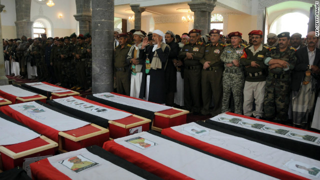 Yemenis pray over the coffins of troops killed when a suicide bomber blew up a vehicle outside a presidential palace in Mukalla on February  27, 2012