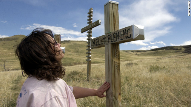 A woman known only as Golden Eagle pray's next to one of the thirteen original crosses April 20, 2004 that was built and placed in Clements Park next to Columbine High School after the shooting on April 20, 1999.