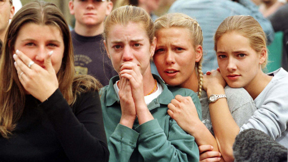 Students from Columbine High School in Littleton, CO watch as the last of their fellow students are evacuated from the school building 20 April 1999 following a shooting spree at the school, which police feared killed as many as 25 people.