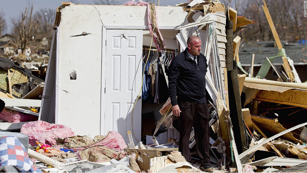 Steve McDonald inspects what's left of his mother-in-law's house in Harrisburg. His in-law, Mary Osman, was among four women and two men killed in the hard-hit town.