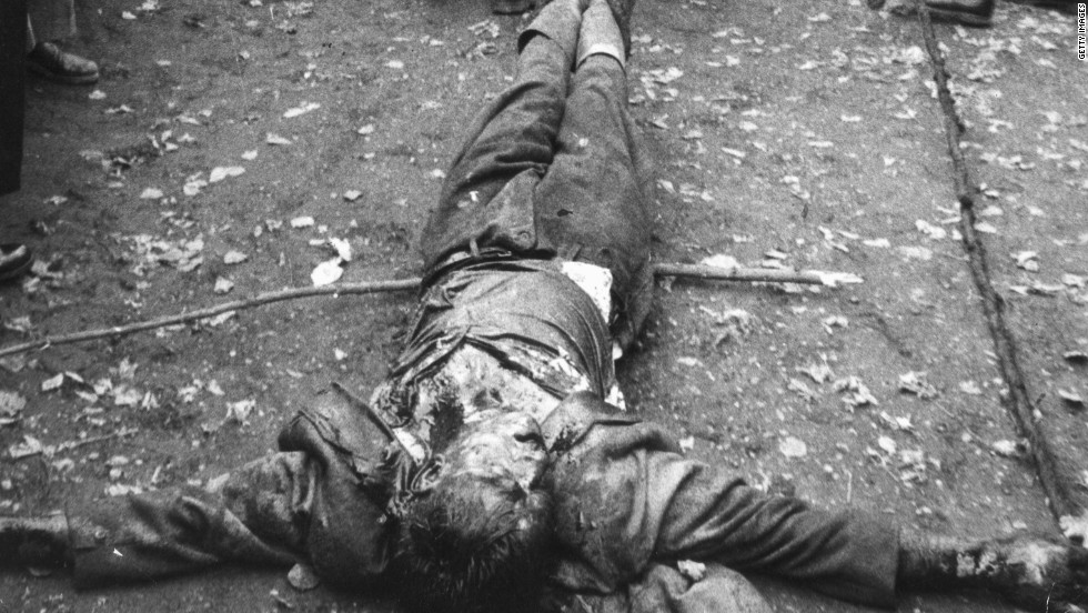 A member of the Hungarian secret police (the AVO) is dragged along the ground by angry protesters during the revolution.