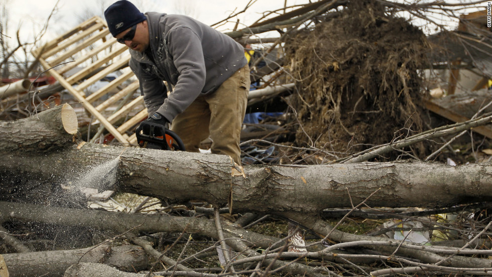 Troy Lewis cuts up a tree on Sunday that fell when a tornado passed through Marysville, Indiana.