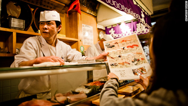 A worker checks stock of fish with a colleague as he prepares to serve Sushi at the Tsukiji fish market