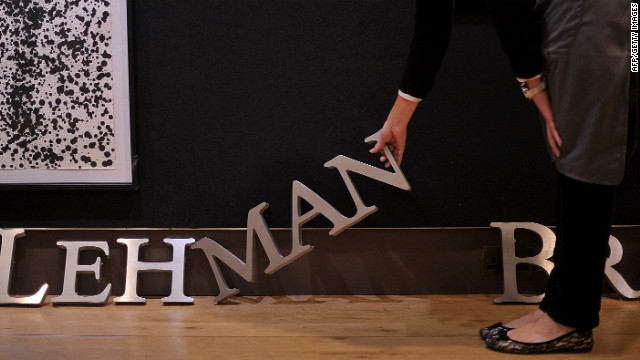 An employee poses for photographers with part of a Lehman Brothers company sign at Christie's auction house in London on September 24, 2010.