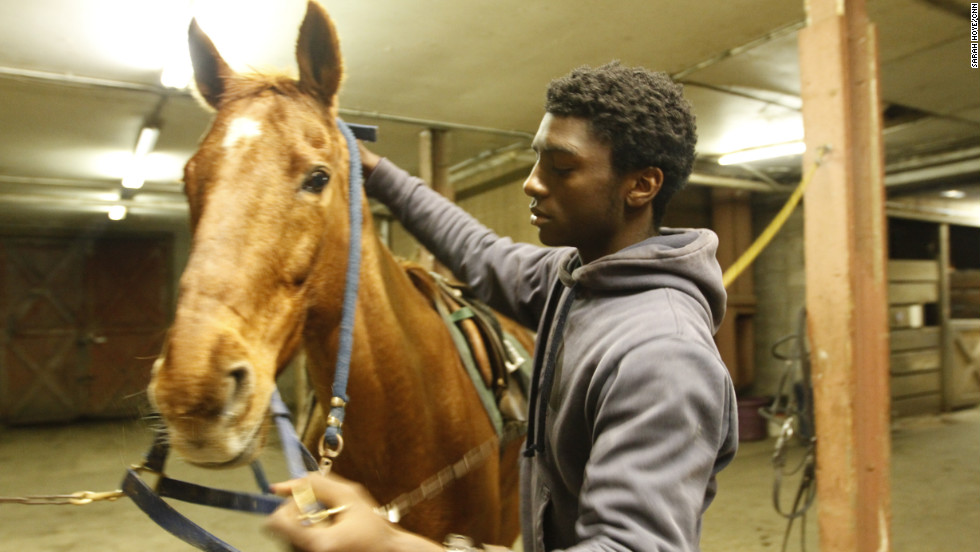 "Kenshaun Walker, 15,  tacks up a horse inside the barn at Work To Ride. Tucked away in the heart of Philadelphia's Fairmount Park, the stable has become an urban oasis for at-risk youth, like Walker, who hail from the city's most dangerous neighborhoods. ""I don't care if I'm not rich. I don't care if my mother's single. I don't care what I don't have. I'm willing to do anything in life to make it to the pros in polo,"" he said."