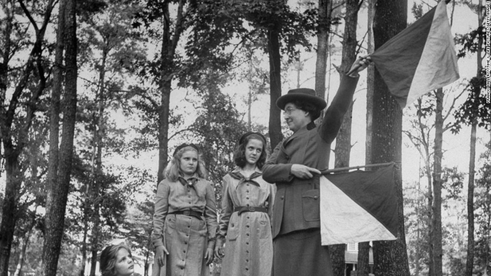 Original caption from LIFE: Signaling, Mrs. Lawrence waves semaphore flags. She can remember most letters up to M, also W (above). She has three children; all were boy scouts