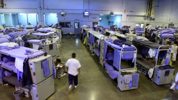 An inmate at the Mule Creek State Prison walks near their bunk beds in a gymnasium that was modified to house prisoners August 28, 2007 in Ione, California.
