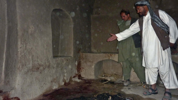 A man points to the spot where he says a family was shot in Kandahar province, Afghanistan, on March 11