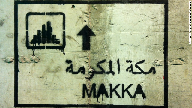 Sarah Mohanna's graffiti features a road sign to Mecca with a cluster of high-rise buildings replacing the Ka'ba shown on genuine street signs