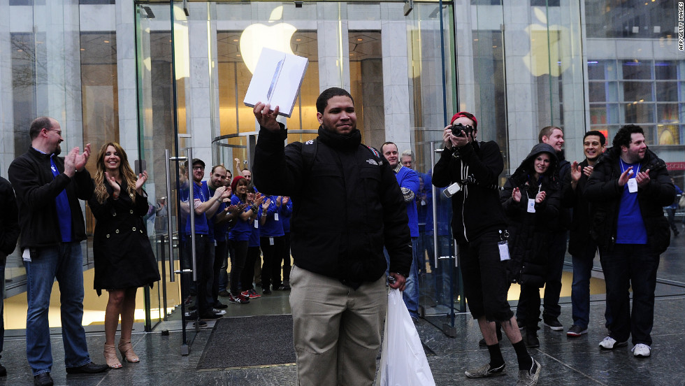 The first customer to purchase a new iPad from the Fifth Avenue Apple store is greeted by cheers and applause.
