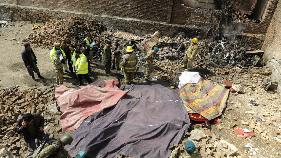 An overhead view shows rescue workers and army personnel at the site of a helicopter crash in Kabul, Afghanistan, on Friday.