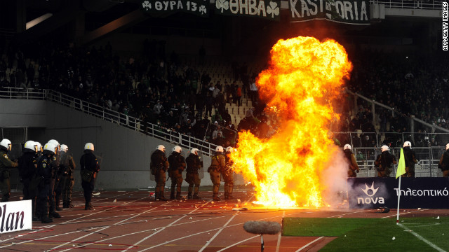 Police battle as fans riot during Olmypiakos and Panathinaikos' match at the Olympic Stadium on Sunday.