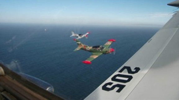 """The view from the cockpit of a SIAI-Marchetti fighter plane ahead of an """"executive dogfight."""""""