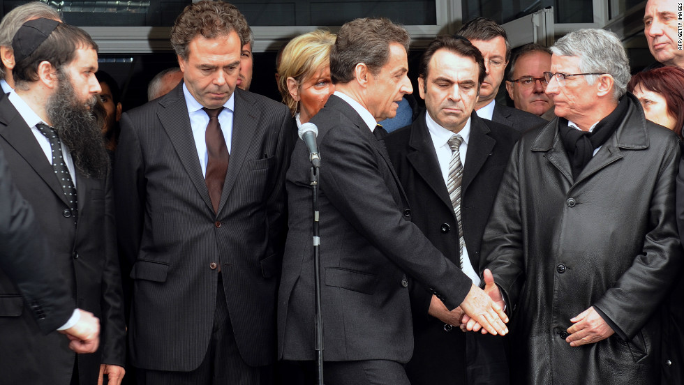 "French President Nicolas Sarkozy shakes hands with the mayor of Toulouse at the Ozar Hatorah school. Sarkozy flew to Toulouse on Monday, after the school shooting took place. He declared ""everything must be done so the killer is arrested."""