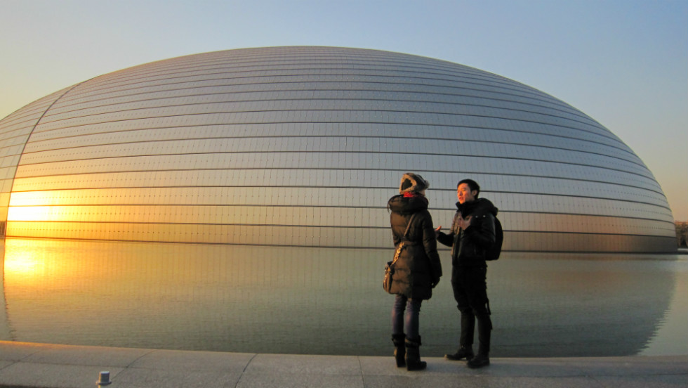 "Rojo went on a ""Fusion Journey"" to Beijing. Chinese choreographer Fei Bo accompanied Rojo on a tour of some of Beijing's cultural focal points. Here, they are seen as the sun sets behind the enormous National Centre for the Performing Arts."