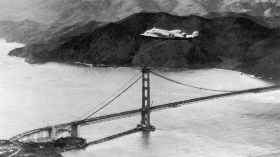 """The Lockheed Electra """"Flying Laboratory,"""" piloted by Amelia Earhart, flies over the Golden Gate bridge in San Francisco, California."""