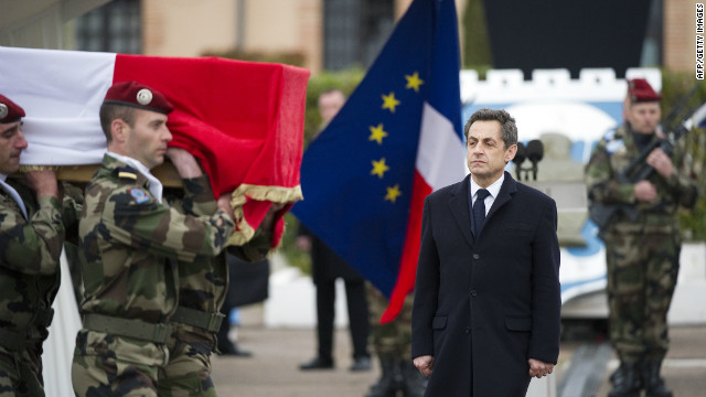French President Nicolas Sarkozy looks on as soldiers carry the coffin of a French paratrooper killed by the Toulouse gunman.