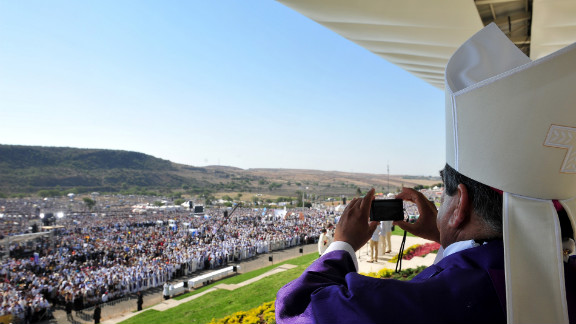A bishop takes pictures during the Mass on Sunday. Cheering onlookers waved balloons, flags and banners as the pope arrived at Bicentennial Park in Mexico's Guanajuato state.