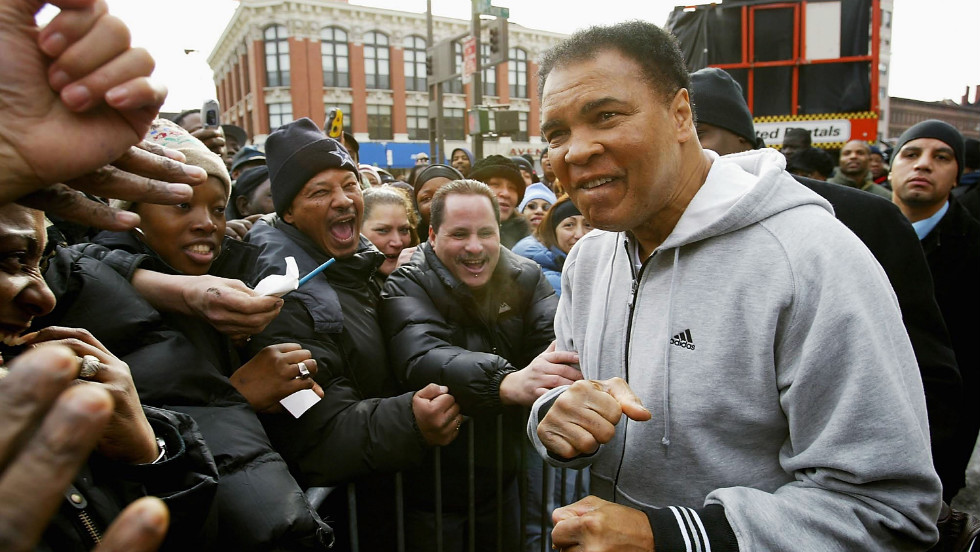 Boxing legend Muhammad Ali greets the crowd in a hoodie before unveiling a new wallscape for Adidas in Harlem.