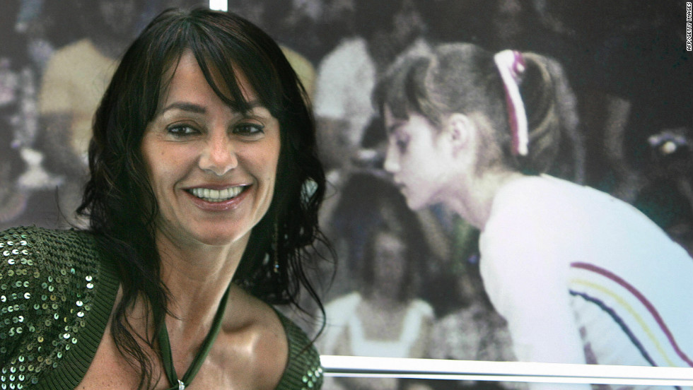 Comaneci, who won five gold medals in two Olympic appearances, stands next to a picture of herself competing at Montreal.