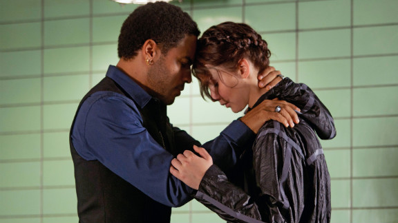 "Lenny Kravitz plays Katniss' stylist Cinna in ""The Hunger Games."" In the novel, Cinna is described as having short brown hair."