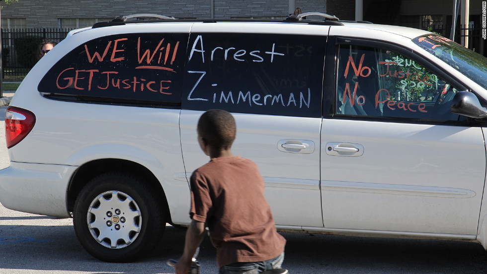 A protest sign painted on the window of a car at a housing project calls for Zimmerman's arrest. For some, the Martin case has become a rallying cry, a chance to air what they believe are years of grievances.