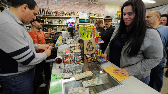 Victoria Vazquez, second from right, buys $280 worth of Mega Millions tickets for her office pool at Liquorland.
