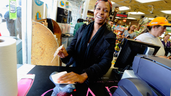 Jasmine Covington, like many Bluebird customers, rubs her Mega Millions ticket against the store's wooden Bluebird statuette for good luck.
