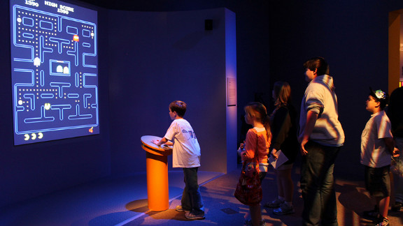 """Kids line up to play a video game that was created before they were born. """"Pac-Man"""" is one of five playable games in the exhibit -- """"Super Mario Brothers,"""" """"Myst,"""" """"Flower"""" and """"The Secret of Monkey Island"""" are the others."""